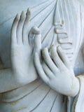 Detalj av en vit staty av Buddha med hans händer Fingrar i mudra arkivbild