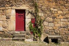 Detalj av ett stenhus med en röd dörr i den historiska byn av Idanha en Velha i Portugal fotografering för bildbyråer