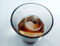 Detalj av exponeringsglas av kallt te med en iskub och en skiva av citronen Arkivbild