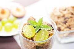 Detalj av exponeringsglas med yoghurt, sädesslag, frukt och mintkaramellen Royaltyfria Bilder