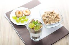 Detalj av exponeringsglas med yoghurten, sädesslag, frukt och mintkaramellen, plommoner arkivbild