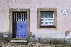Detalj av fasaden av ett färgrikt hus i den historiska byn av Castelo Mendo med en dörr och ett fönster, i Portugal Royaltyfri Bild