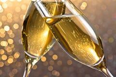 Detalj av flöjter för en champagne med guld- bubblor på ljus bokehbakgrund Royaltyfri Bild