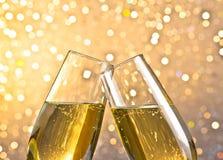 Detalj av flöjter för en champagne med guld- bubblor på ljus bokehbakgrund Arkivfoton