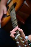 Detalj av gitarren med barnhänder Arkivfoto