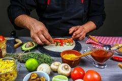 Detalj av händer av den manliga förberedande tortillan, händer av kockinnehavburritoen tacos för grön mexikansk sås för kokkonst  royaltyfri bild