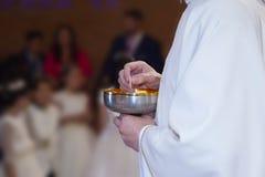 Detalj av händerna av en präst på den tiden av att ge den första nattvardsgången till barn royaltyfri bild