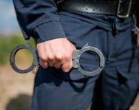 Detalj av handbojor för ett polisinnehav arkivfoton