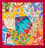 Detalj av handen - gjort patchworktäcke i rött inrama Arkivfoto