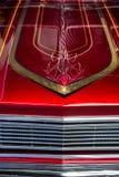 Detalj av huven av en röd och krombil med hand-målade linjer royaltyfri foto