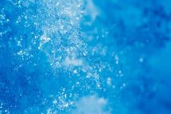 Detalj av iskristallen och snöflingor, blå bakgrund Royaltyfri Bild