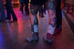 Detalj av kängorna och de tattoed benen av en ung kvinna i den brutna ekerdansstället i Austin, Texas Fotografering för Bildbyråer