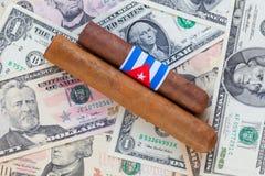 Detalj av lyxiga kubanska cigarrer på US dollar Arkivbild