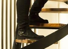 Detalj av manlig bärande svart jeans och svarta mockaskinnkängor som upp klättrar trappan Brott inbrott, säkerhetsbegrepp arkivfoton