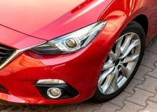 Detalj av pannlampan av en modern röd bil med stilfull sportig design Royaltyfri Foto