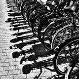 Detalj av parkerade cyklar med skuggor på trottoaren i Amsterdam Fotografering för Bildbyråer