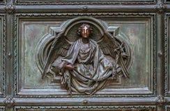 Detalj av Pietaplatsen i basrelief på Milan domkyrkadörrar royaltyfri fotografi