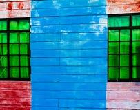 Detalj av Röd-blått träväggen med gröna Windows Royaltyfri Fotografi