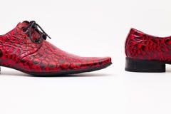 Detalj av röda skor för man` s på den vita tabellen Fotografering för Bildbyråer