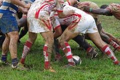 Detalj av rugbyspelare som har gyckel i ett lerigt fält royaltyfri foto