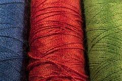Detalj av rullar av trådar, blått som är röda, gräsplan Royaltyfria Bilder
