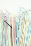 Detalj av svart dricka sugrör för singel in i en grupp av färgrika sugrör Arkivfoton