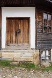 Detalj av tappningträdörren och fönster av det gamla wood huset arkivbild