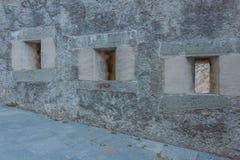 Detalj av tre slitsar av en gammal slott Royaltyfri Foto