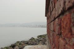 Detalj för vägg för röd tegelsten med havslandskap Arkivfoton