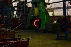 Detalj - formdel av en gjuten maskin Varmt järn i smeltery rymde vid en arbetare royaltyfri foto