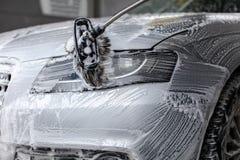 Detalj på främre ljus för bil som tvättar sig med tvålskum royaltyfri fotografi