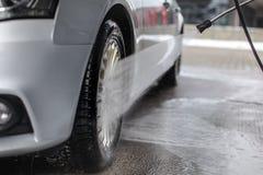 Detalj på silverbilframhjulet som tvättar sig med strålvattenspr arkivfoton