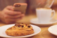 Detaljbild av den unrecognisable mannen som dricker den smarta telefonen för kaffe och för innehav, medan ha frukosten i restaura Fotografering för Bildbyråer