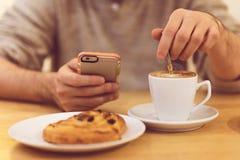 Detaljbild av den unrecognisable mannen som dricker den smarta telefonen för kaffe och för innehav, medan ha frukosten i restaura Arkivbild