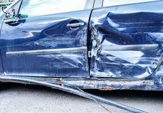 Detaljen av den kraschade bilen efter olycka, blåa metallplattor på sidodörr deformerade royaltyfri foto