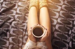 Detaljen av den sexiga unga kvinnan och solen tänder Kvinnauppehälle per kaffekoppen och läst en bok royaltyfri bild