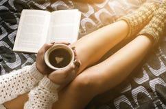 Detaljen av den sexiga unga kvinnan och solen tänder Kvinnauppehälle per kaffekoppen och läst en bok arkivbilder