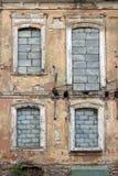 Detaljen av en forntida och sliten vägg med tegelsten fyllde in fönster Arkivbild