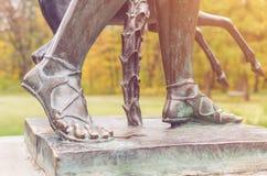 Detaljen av en skulptur av brons lägger benen på ryggen på en sockel arkivbild