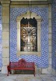 Detaljen av fasaden av ett hus med en röd metallbänk och ett fönster med ett järn fäktar surrounde Royaltyfri Bild