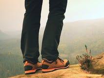 Detaljen av fotvandraren lägger benen på ryggen i svart apelsin som fotvandrar kängor på bergtoppmöte Fot i trekking skor Arkivbild