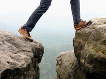 Detaljen av fotvandraren lägger benen på ryggen i svart apelsin som fotvandrar kängor på bergtoppmöte Fot i trekking skor Arkivbilder
