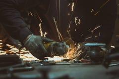 Detaljen av handen genom att använda en molar för att klippa ett stycke av metall och göra gristrar Arkivbild