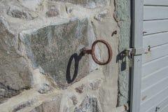 Detaljen av smidesjärn hakar fäst till stenväggen på ret royaltyfri foto