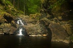 Detaljen av vaggar med den lilla vattenfallet på den svarta flodklyftan Royaltyfri Fotografi