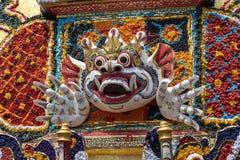 Detaljen bjöd kremeringtornet med traditionella balineseskulpturer av demoner och blommor på den centrala gatan i Ubud, ön Bali, arkivfoton