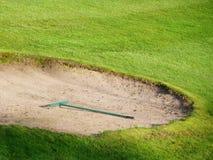 Detaljen för golfbanasandgropen krattar royaltyfri bild
