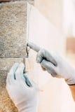 detaljer av arbetarhänder som rappar och installerar stenen på konstruktionsplats perfektiondetaljer i konstruktionsbransch royaltyfria bilder