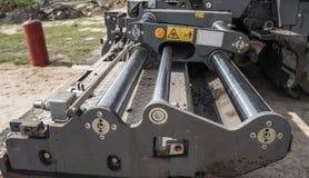 Detaljer av asfaltpavermaskinen under vägkonstruktion och repareraarbeten En paverefterbehandlare, asfaltefterbehandlare eller arkivfoton