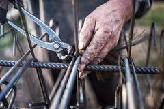 Detaljer av byggnadsarbetaren - händer som säkrar stålstänger med trådstången för förstärkning av betong Royaltyfri Fotografi